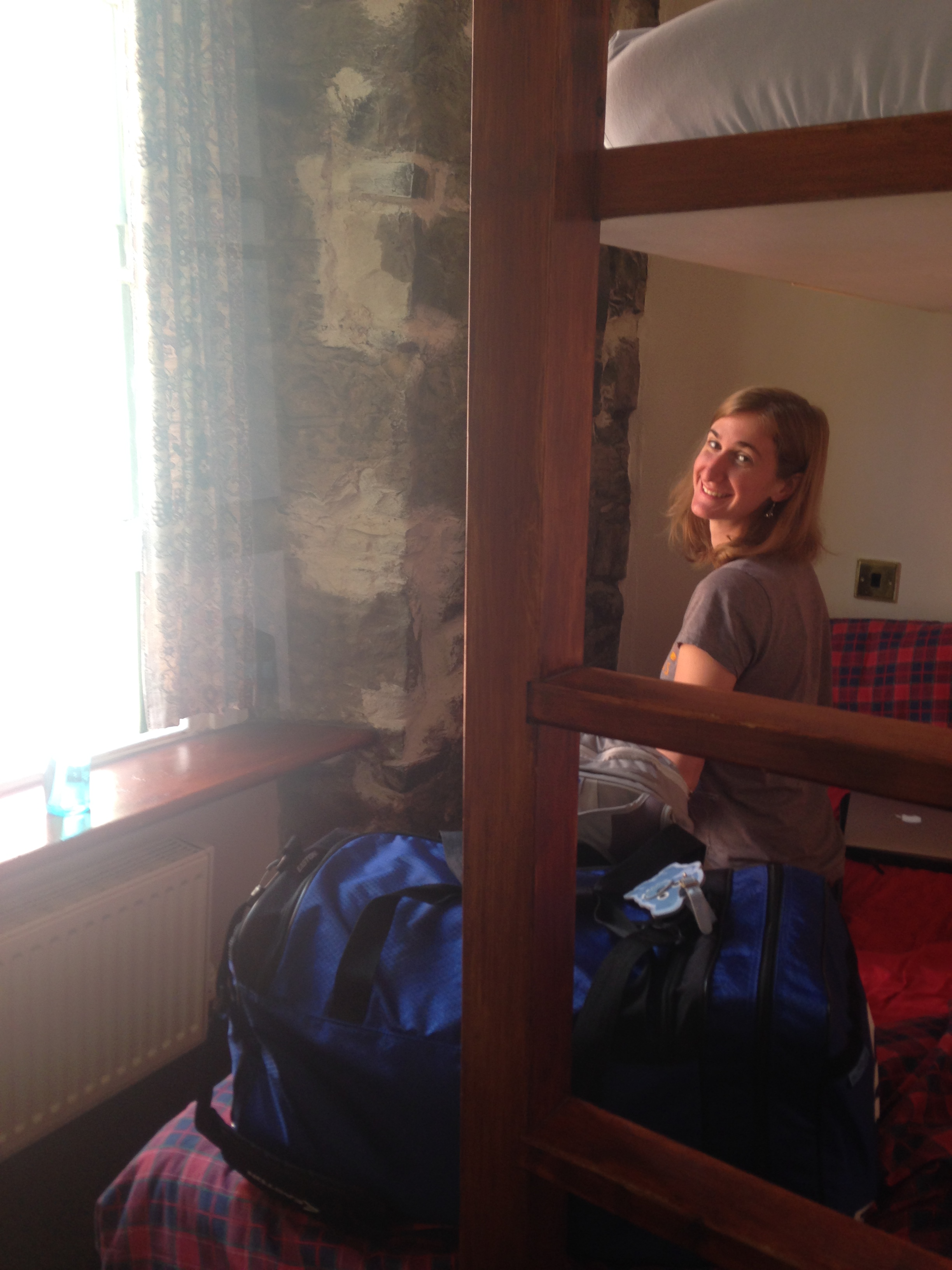 A picture of my friend Kate sitting on our bunk bed.