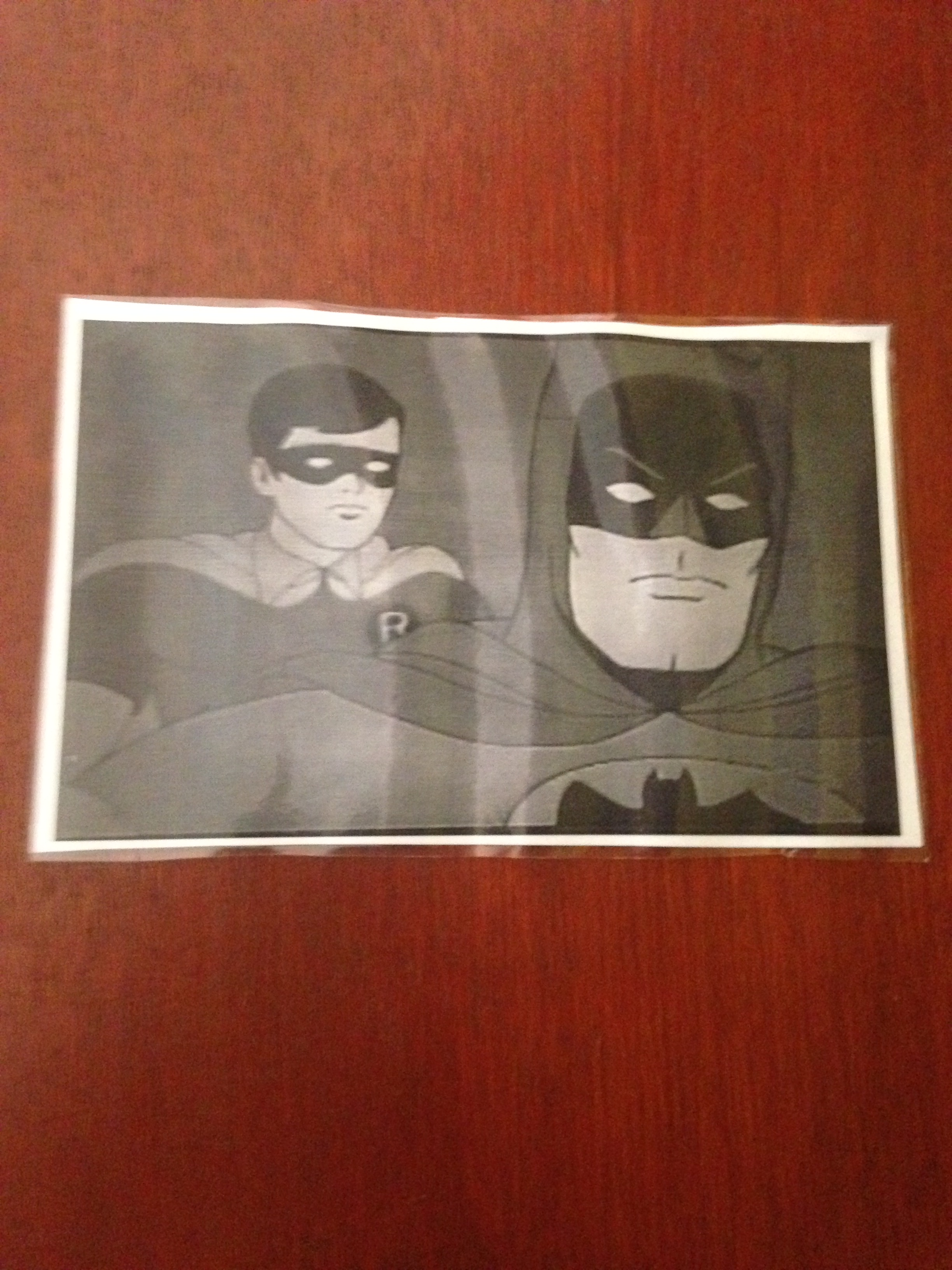 A picture of a brown door with another black and white picture of the old Batman and Robin cartoon taped to it.