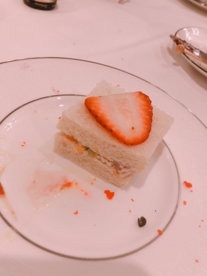a picture of a strawberry chicken salad sandwich. teas-size, white bread with a prominent strawberry slice on top.